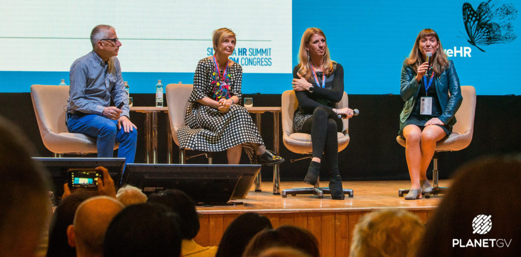 A panel of four speakers seated on the stage