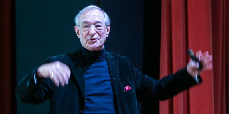 Pierre Casse speaks animatedly on stage